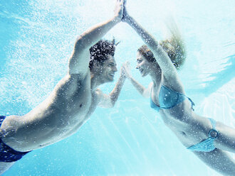 Couple touching hands underwater - CAIF07762