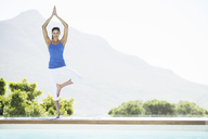 Woman practicing yoga at poolside - CAIF07774