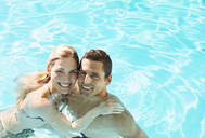 Portrait of smiling couple in swimming pool - CAIF07801