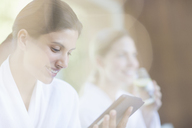 Woman using digital tablet at spa - CAIF07804