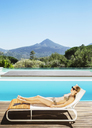 Woman relaxing on lounge chair at poolside - CAIF07825