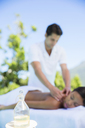 Woman receiving massage on spa patio - CAIF07831