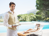 Waiter smiling at poolside - CAIF07843