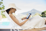 Woman using digital tablet on lounge chair at poolside - CAIF07846
