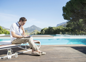 Man using laptop at poolside - CAIF07849