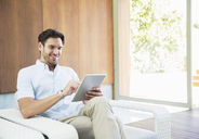 Man using digital tablet in armchair - CAIF07852