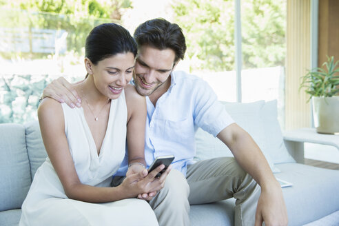 Couple using cell phone on sofa - CAIF07855