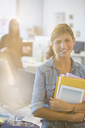Portrait of businesswoman smiling in office - CAIF07873