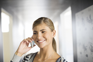 Businesswoman talking on cell phone in office - CAIF07909