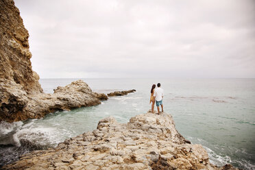 Rear view of couple standing on rock at beach - CAVF01365