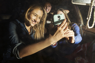 Happy friends taking selfie while sitting in car - CAVF01371