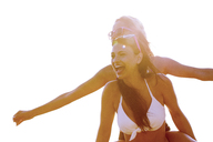 Low angle view of woman piggybacking friend against clear sky - CAVF01377