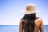 Rear view of woman wearing sun hat standing against clear sky - CAVF01452