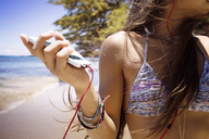 Woman listening music on mobile phone while standing at beach - CAVF01461