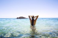 Rear view of woman with hands behind head standing in sea against clear sky - CAVF01464