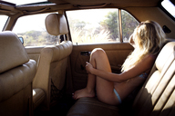 Side view of woman sitting in car - CAVF01473