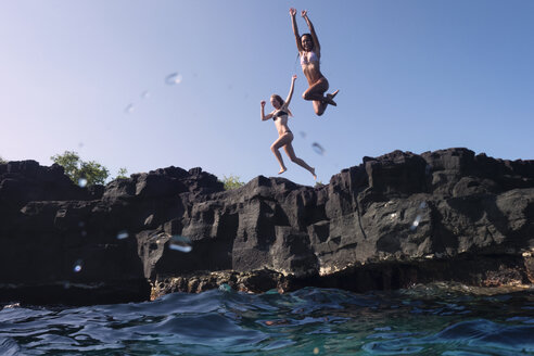 Friends jumping from cliff into sea - CAVF01485