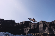 Woman carrying surfboard while walking on rocks against clear sky - CAVF01488