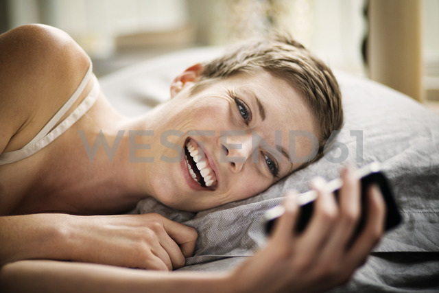 Smiling woman looking at smart phone while lying on bed - CAVF01518