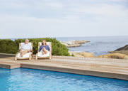 Senior couple relaxing at poolside - CAIF07938