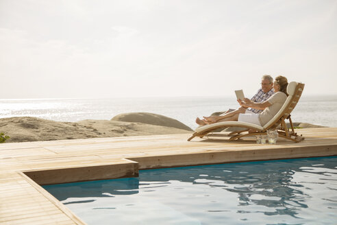 Older couple relaxing by pool - CAIF07947