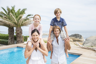 Family smiling by swimming pool - CAIF07953