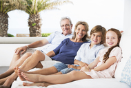 Older couple and grandchildren relaxing on sofa - CAIF07962