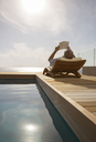 Man reading in lawn chair by pool - CAIF07965