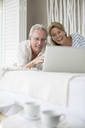 Older couple using laptop on bed - CAIF07971