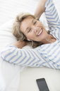 Older woman listening to earphones on bed - CAIF07977
