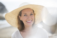Older woman wearing straw hat on beach - CAIF07989