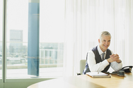 Businessman smiling at desk in office - CAIF08001