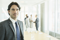 Businessman smiling in conference room - CAIF08004