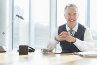 Businessman smiling at desk in office - CAIF08007
