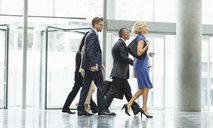 Business people walking in office lobby - CAIF08010