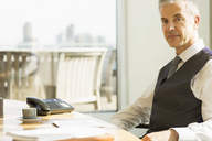 Businessman sitting at desk in office - CAIF08022