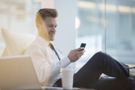 Businessman using cell phone in office - CAIF08037