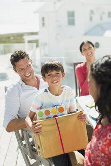 Family celebrating birthday on sunny patio - CAIF08046