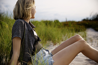 Side view of woman sitting on sand - CAVF01566