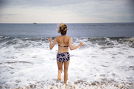 Rear view of woman running on shore at beach - CAVF01581