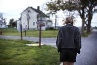 Rear vi3ew of woman walking in road - CAVF01584
