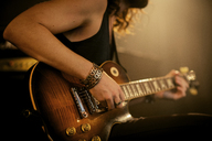 Midsection of man practicing guitar in rock music studio - CAVF01587