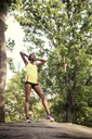 Woman exercising while standing on tree trunk - CAVF01611