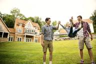 Happy men swinging girl in backyard - CAVF01683