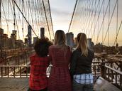 Rear view of friends standing by railing on Brooklyn Bridge - CAVF01713