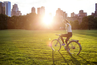 Woman with arms outstretched cycling in Central Park - CAVF01740