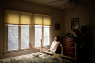Woman sitting by window at home - CAVF01848