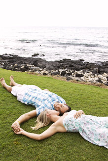 Couple holding hands while lying on field - CAVF01929