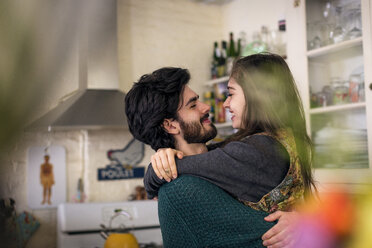 Happy couple embracing while standing at kitchen - CAVF02058