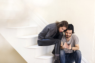 Couple looking at smart phone while sitting on staircase - CAVF02061